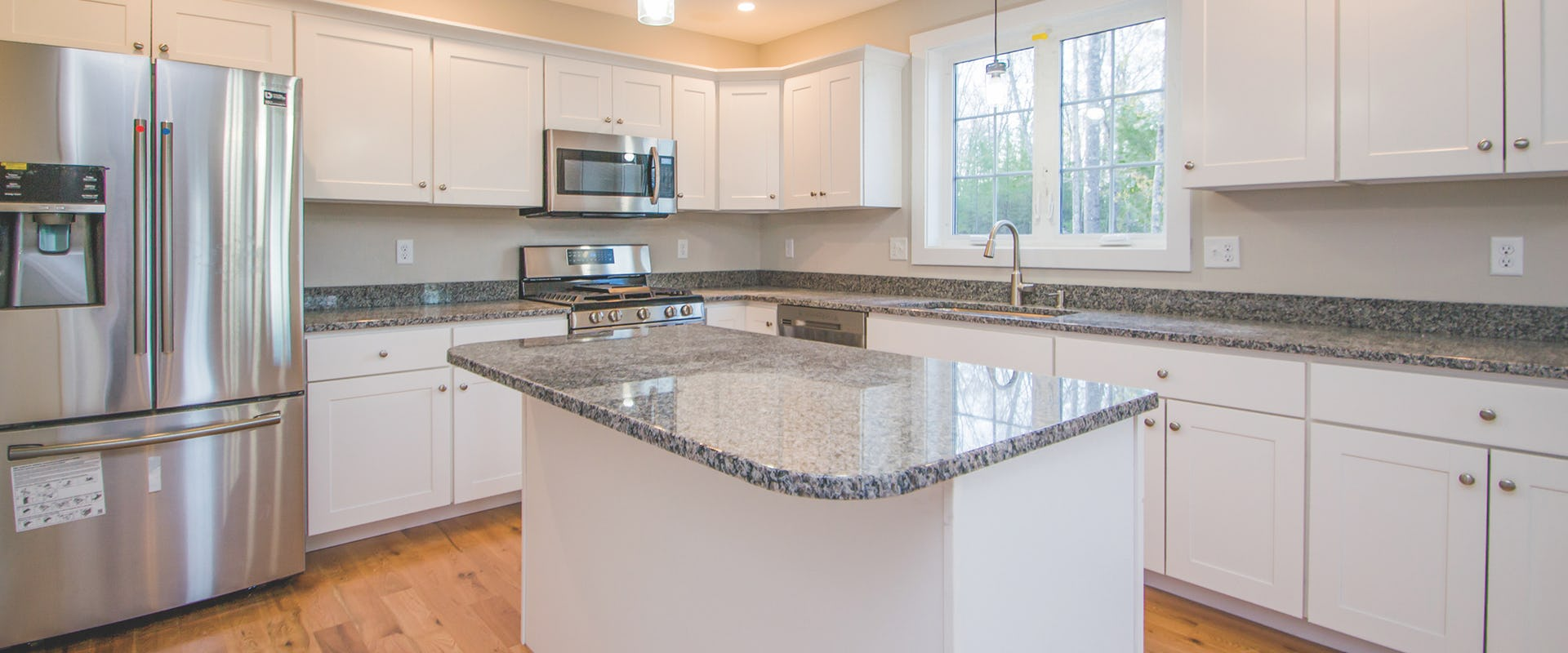 white kitchen with granite counters in new home